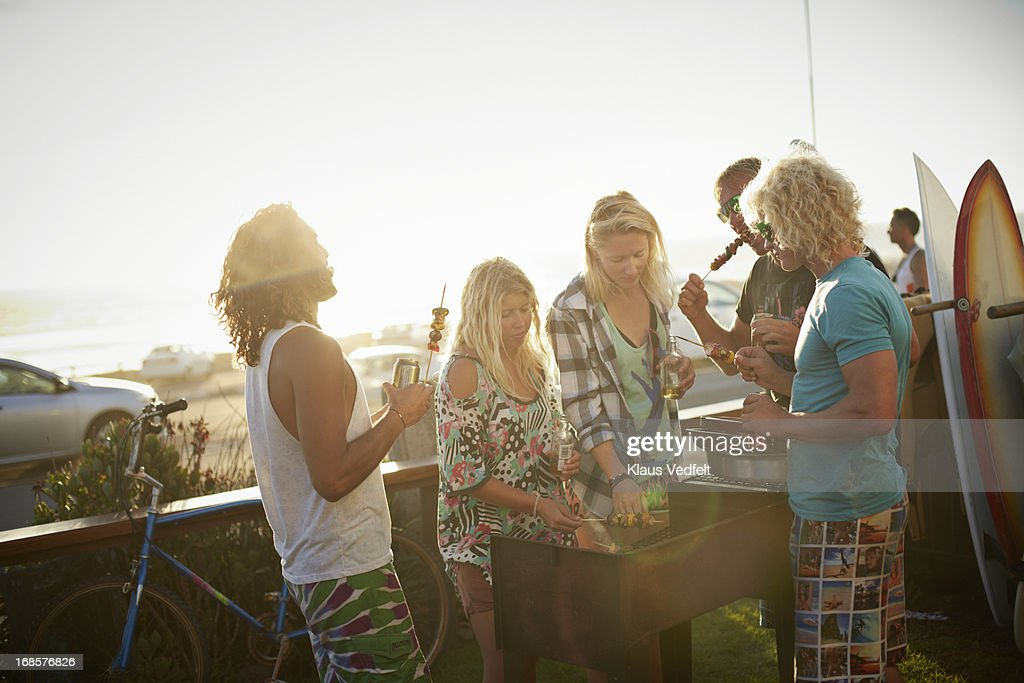 Surfer friends doing BBQ in beachhouse garden : Stock Photo
