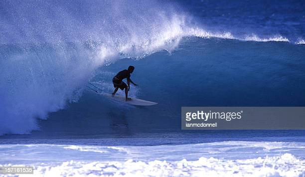 surfer getting barrelled - banzai pipeline stock photos and pictures