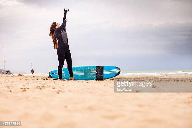 Surfer getting dressed before jumping into the water