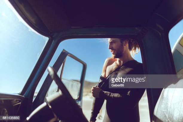 surfer getting ready - muscle men at beach stock photos and pictures