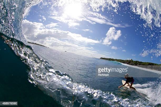 Surfer girl bottom turns towards the wave