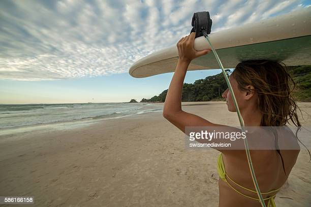 Surfer girl carrying surfboard to the ocean