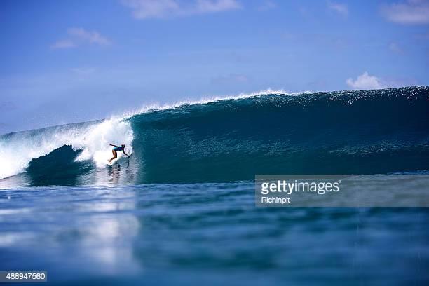 Surfeuse gouttes dans une grosse vague idéale à gauche