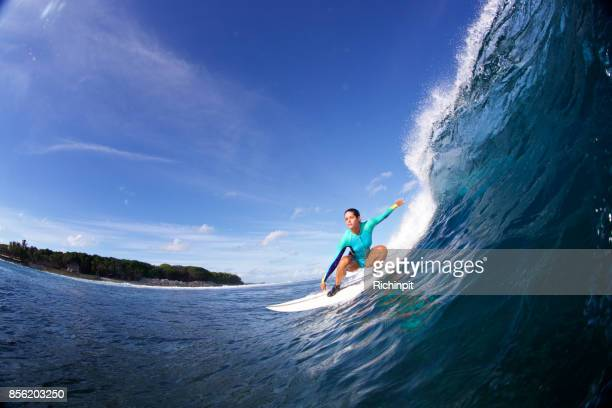 Surfer girl drops into a wave