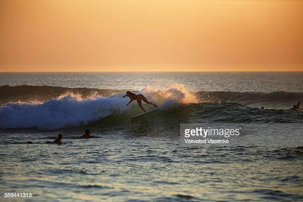 Surfer girl in sunset surfing