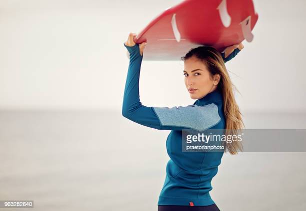 Surfer girl is standing on the beach