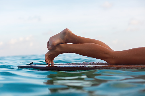 Surfer girl lying on surfboard