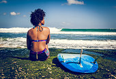 http://www.istockphoto.com/photo/surfer-girl-sitting-next-to-blue-longboard-on-the-coral-reef-gm818873792-132954749