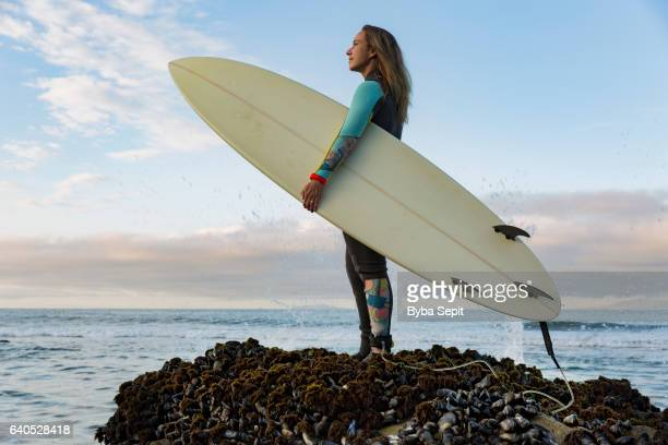 Surfer Girl Standing on Top of Ocean Rock Holding Surfboard
