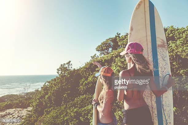 Surfer girls going to the sea