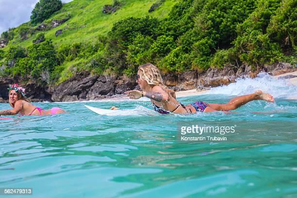 Surfer girls in ocean water.