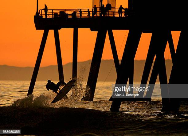 A surfer goes airborne amid a golden sunset at the Huntington Beach pier as surf heights build Tuesday High surf and large swells are expected to...