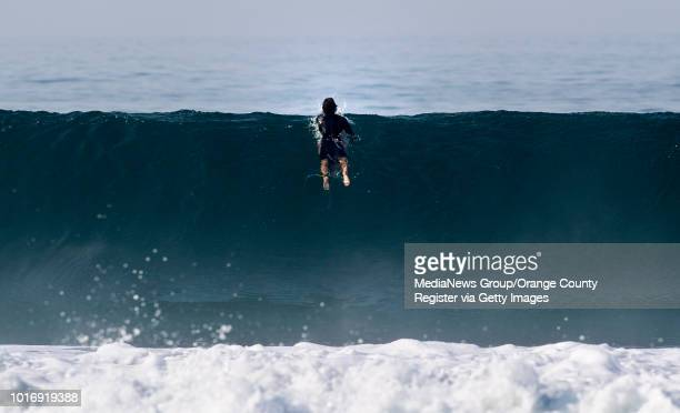 A surfer goes over the crest of a swell in Newport Beach on Friday August 10 2018 A swell from Hurricane John will bring larger waves to southfacing...