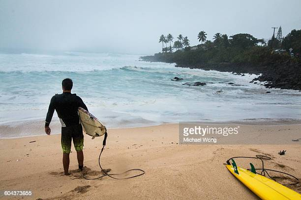 surfer going out at waimea bay - waimea bay - fotografias e filmes do acervo