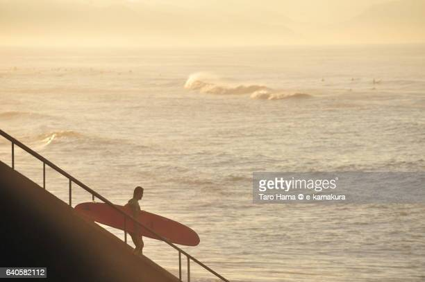 A surfer going to beach in the morning