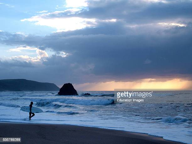 Surfer heading for the sea at sunset Widemouth Bay Bude Cornwall UK