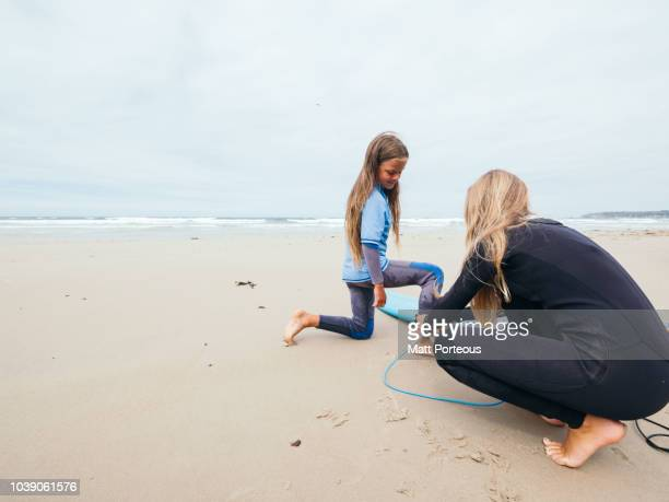 Surfer helps other with leash