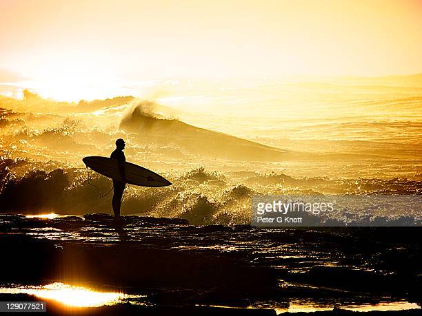 Surfer holding surfboard on rocks