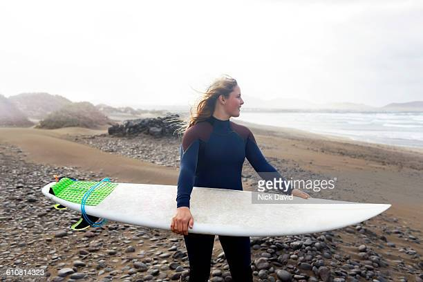 Surfer holding surfboard on the beach