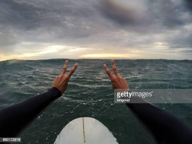 Surfeur tenant le signe de la victoire en mer