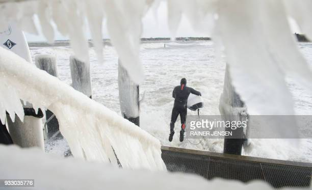 TOPSHOT A surfer in a neoprene suit jumps from icy stairs into the Baltic Sea that is lashed by the wind on March 17 2018 in Timmendorfer Strand...