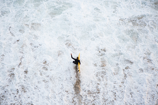 Surfer in black wet suit walking into turbulent waters carrying yellow surfboard - gettyimageskorea