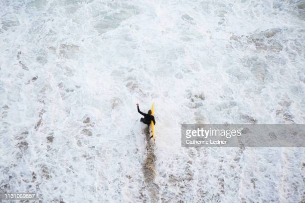 Surfer in black wet suit walking into turbulent waters carrying yellow surfboard