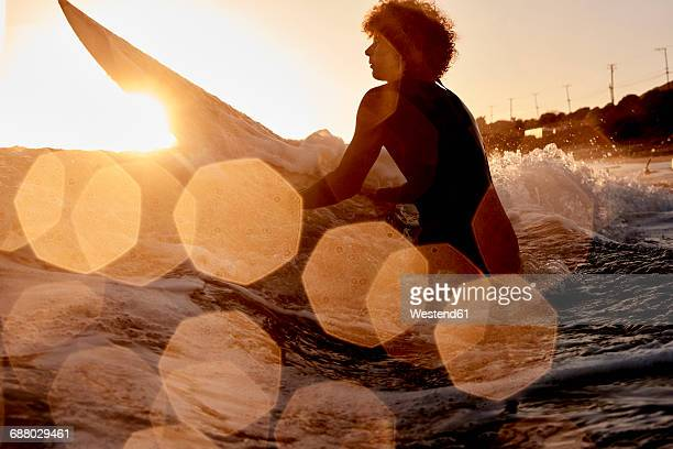 Surfer in the sea at sunset