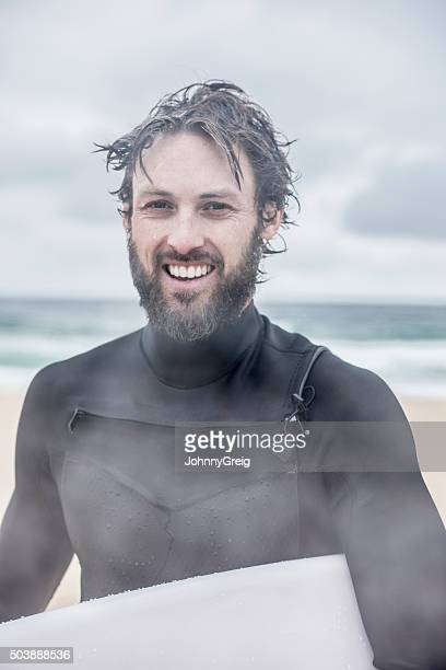 Surfer in wetsuit with surfboard and wet hair