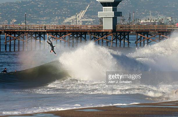 A surfer is ejected after getting a coveted tube ride as the third major El Niño storm of the season brings high surf at the Seal Beach pier in Seal...