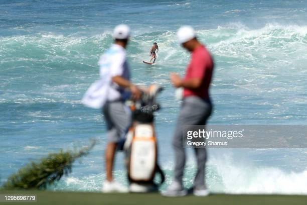 Surfer is seen as Jon Rahm of Spain stands on the 11th green during the final round of the Sentry Tournament Of Champions at the Kapalua Plantation...