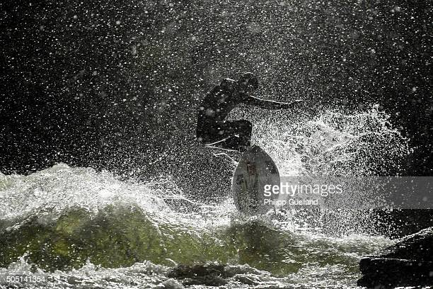 A surfer is silhouetted under floodlights in dense snowfall as he takes turns on the Eisbach river in the English Garden on January 15 2016 in Munich...