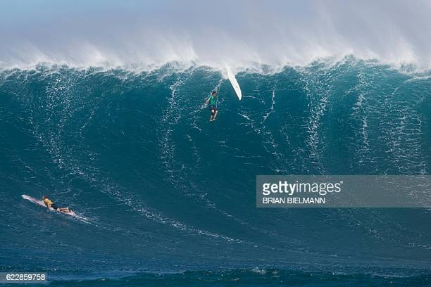 Surfer is wiped out by a big wave as another one paddles out to escape it during the Big Wave surfing Peahi Challenge 2016 at Jaws, off the coast of...
