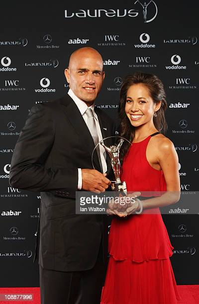 """Surfer Kelly Slater of the United States and guest pose with his award for """"Laureus World Action Sportsperson of the Year"""" in the winners studio at..."""