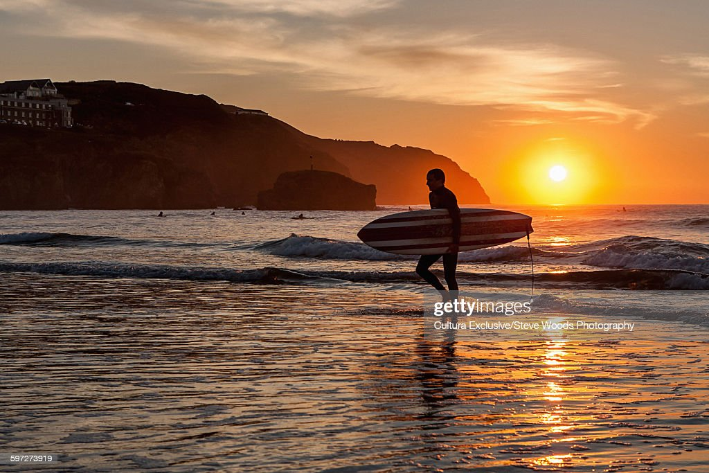 fa58e558ab Surfer Leaving The Ocean At Sunset Perranporth Cornwall Uk Stock ...