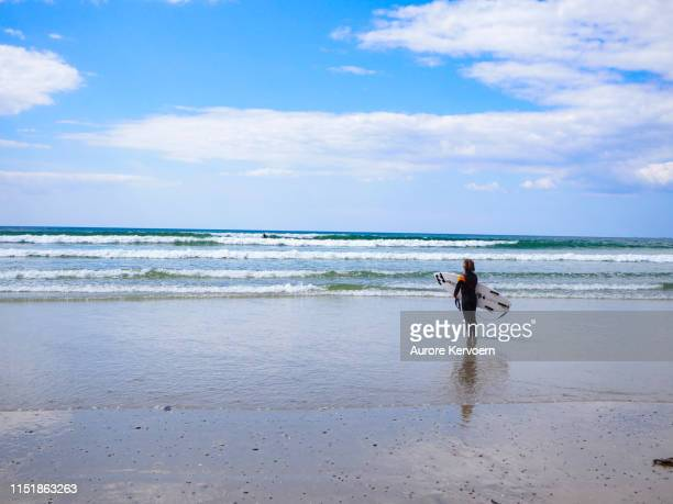 """surfer looking at the horizon on the """"pointe de la torche"""" in brittany, plomeur, france - finistere stock photos and pictures"""