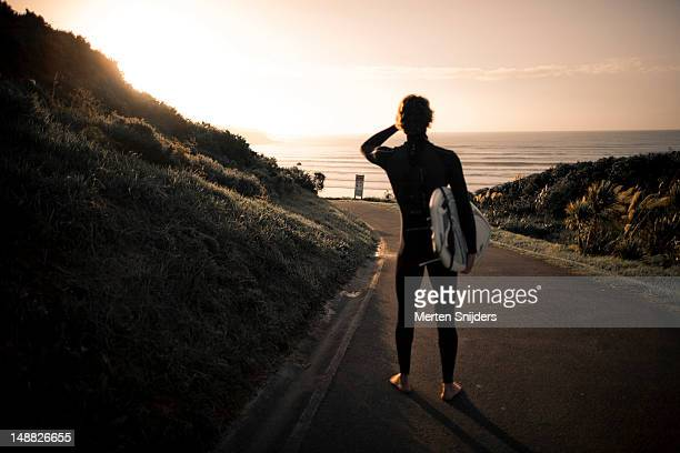Surfer looking at the incoming waves from the road.