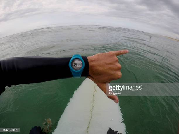 Surfer looking at wrist watch in the sea (point of view)