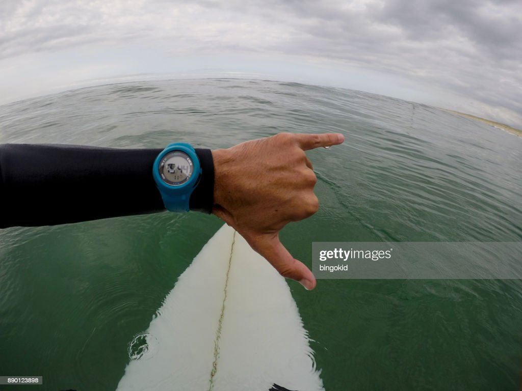 Surfer looking at wrist watch in the sea