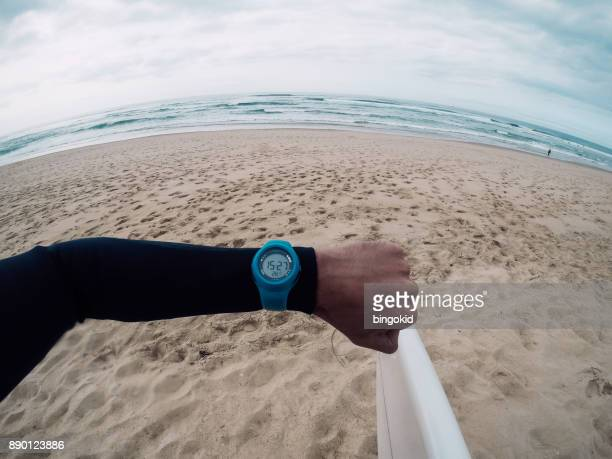 Surfer looking at wrist watch on the beach