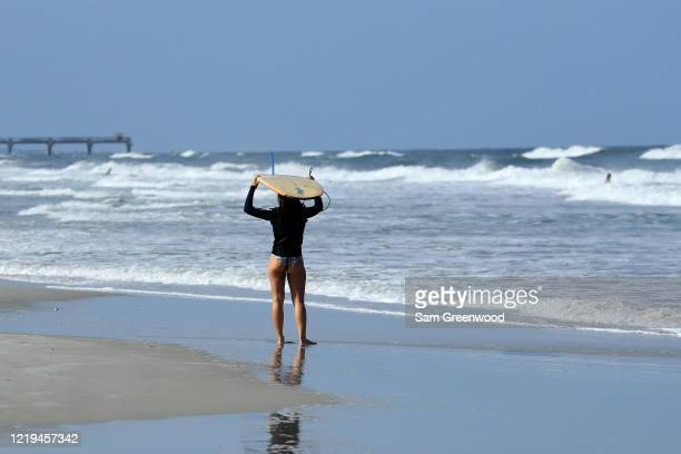A surfer looks at the waves on April 17 2020 in Jacksonville Beach Florida Jacksonville Mayor Lenny Curry announced Thursday that Duval County's...