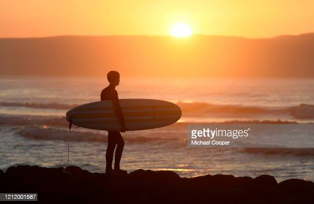 A surfer looks out to sea at sunset on a deserted Castlerock Beach Co Londonderry on May 6 2020 in Castlerock Northern Ireland The UK is continuing...