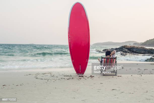 Surfer man and his red surfboard
