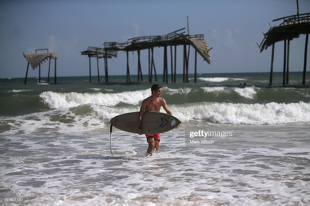 Surfer Nick Haven looks for a place to surf near the old damaged Hatteras Pier, July 2, 2014 in Cape Hatteras, North Carolina. A Hurricane watch has been issued for North Carolina's Outer Banks due to approaching Tropical Storm Arthur that is expected to gain strength.