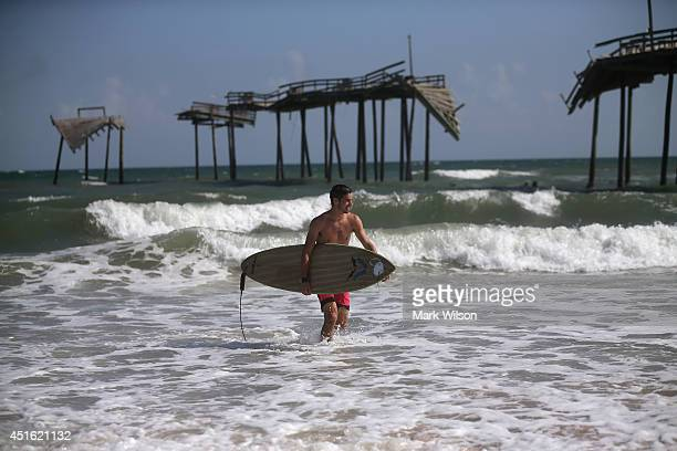 Surfer Nick Haven looks for a place to surf near the old damaged Hatteras Pier July 2 2014 in Cape Hatteras North Carolina A Hurricane watch has been...