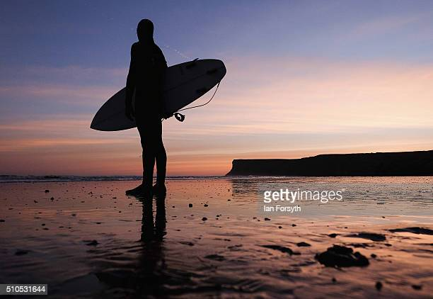 Surfer Nick Woodings heads out for a morning surf as the sun begins to rise over the beach on February 16 2016 in SaltburnbytheSea England...