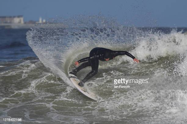 Surfer Nick Woodings rides a wave as he surfs on the north east coast on October 04, 2020 in Redcar, England.