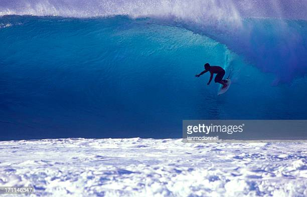 surfer on a blue wave - waimea bay hawaii stock photos and pictures