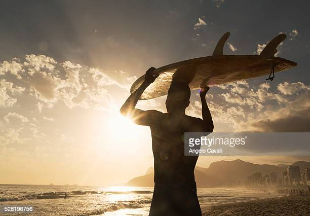 Surfer on beach at sunset holding surfboard, Rio De Janeiro, Brazil