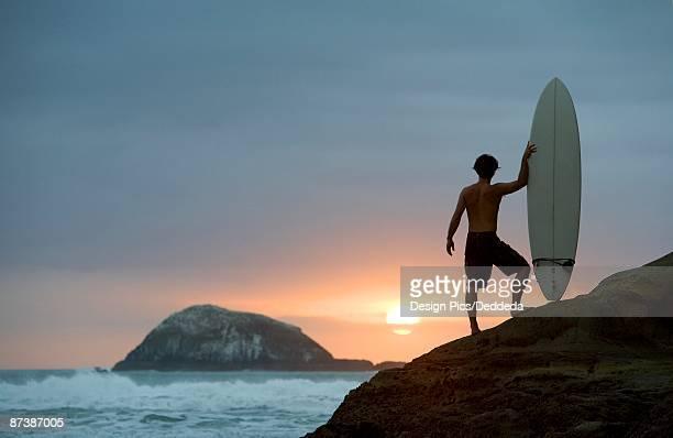 A surfer on Muriwai Beach, New Zealand
